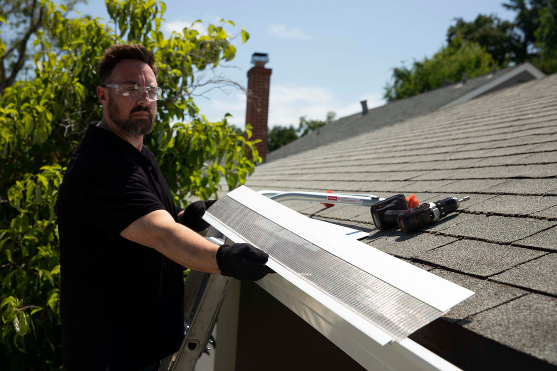 Photo shows a tech placing a gutter guard onto the gutter of the roof.