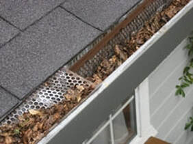 Photo shows the gutter of the roof which is full of brown leaves and a broken gutter guard.